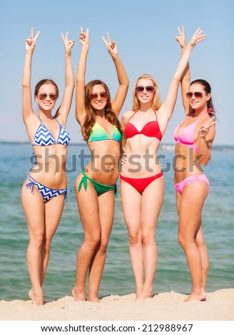 summer vacation, holidays, gesture, travel and people concept - group of smiling young women showing peace or victory sign on beach - stock photo