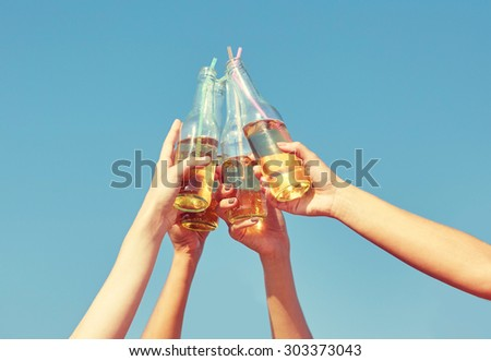summer vacation, holidays, party and people concept - close up of many hands clinking bottles with lemonade or beer over blue sky background - stock photo
