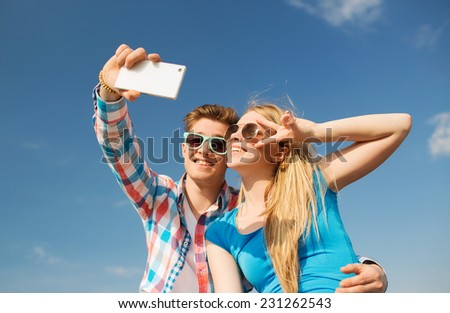 summer, vacation, holidays, technology and friendship concept - smiling couple with smartphone making selfie outdoors - stock photo
