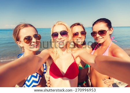 summer vacation, holidays, travel and people concept - group of young smiling women photographing by camera or smartphone on beach - stock photo