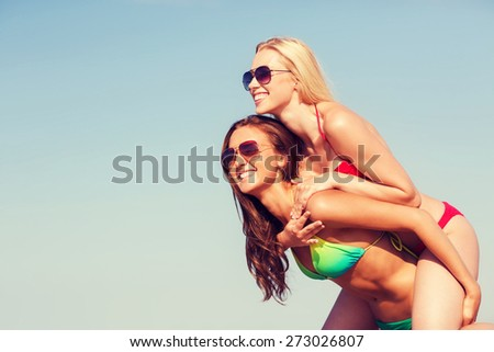 summer vacation, holidays, travel, friendship and people concept - two smiling young women on beach - stock photo