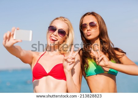 summer vacation, holidays, travel, technology and people concept - two smiling young women on beach making selfie with smartphone over blue sky background - stock photo