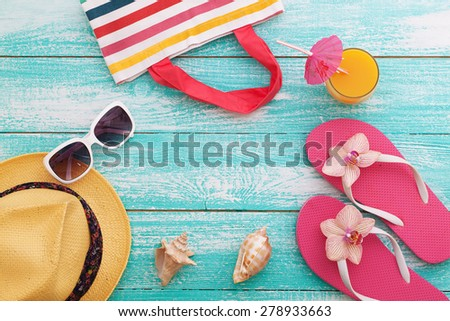 Summer vacation. Pink sandals and beach accessories on wooden background. Flat mock up for design. - stock photo