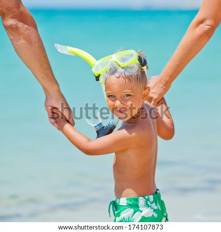 Summer vacation - Portrait of happy boy in face masks and snorkels, sea in background. - stock photo