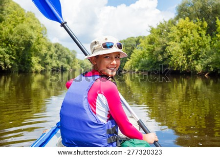 Summer vacation - Portrait of happy cute girl kayaking the on river, enjoying a lovely summer day - stock photo