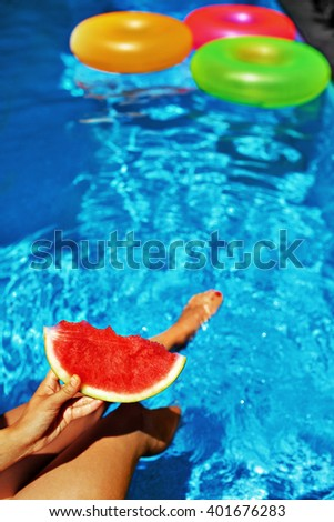 Summer Vacation. Summertime Fun. Female Hand Holding Slice Of Ripe Juicy Watermelon By The Swimming Pool. Colorful Floating Rings In Refreshing Blue Water On Background. Freshness, Enjoyment Concept - stock photo