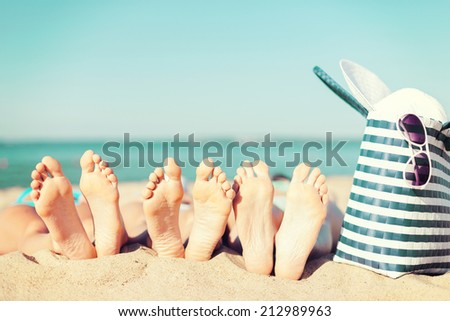 summer vacation, sunbathing and pedicure concept - three women lying on the beach with straw hat, sunglasses and bag - stock photo