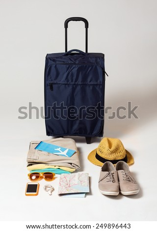 summer vacation, tourism and objects concept - travel bag, map, air ticket and clothes with personal stuff - stock photo