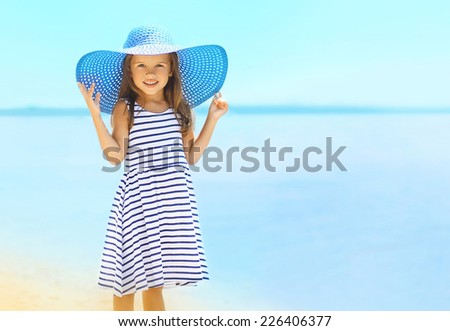 Summer, vacation, travel and people concept - pretty little girl in a striped dress and summer hat relaxing on the beach near sea - stock photo