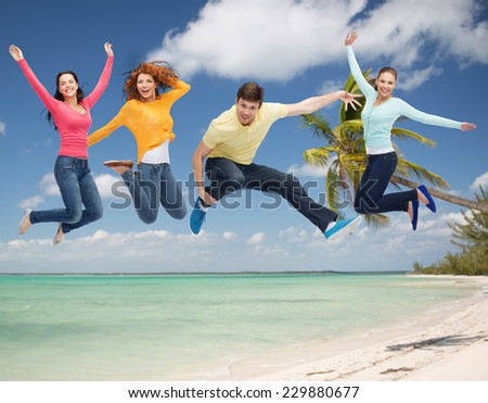 summer vacation, travel, freedom, friendship and people concept - group of smiling teenagers jumping in air over tropical beach background - stock photo