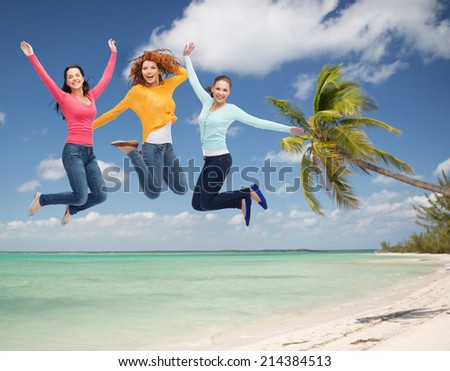summer vacation, travel, freedom, friendship and people concept - group of smiling young women jumping in air over tropical beach background - stock photo
