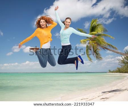 summer vacation, travel, freedom, friendship and people concept - smiling young women jumping in air over tropical beach background - stock photo