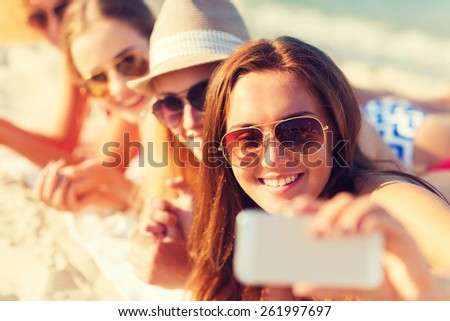 summer vacation, travel, technology and people concept - close up of smiling women in sunglasses and hats making selfie with smartphone on beach - stock photo
