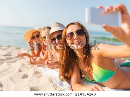 summer vacation, travel, technology and people concept - group of smiling women in sunglasses making selfie with smartphone on beach - stock photo