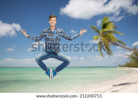 summer vacation, travel, tourism, freedom and people concept - smiling young man hanging of flying in air in pose of yoga over tropical beach background - stock photo