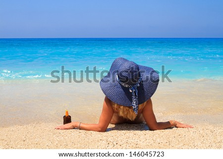 Summer vacation woman on the beach in beach straw hat holding a sun lotion bottle and looking at the ocean - stock photo