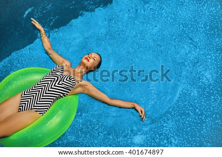 Summer Vacations. Beautiful Sexy Smiling Woman With Perfect Fit Body, Healthy Skin In Swimwear Sunbathing, Floating On Float Swim Ring In Swimming Pool Water. Enjoyment. Beauty, Wellness. Recreation - stock photo