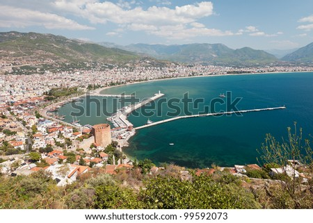 Summer vacations - blue Mediterranean sea and Turkey Alanya east coast beach resort with lighthouse and ship bay view from ancient mountain castle wall - stock photo