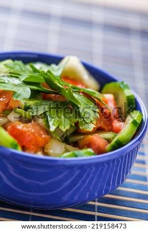 summer vegetable salad with tomatoes and cucumbers garnished with parsley sprig in blue deep bowl, next is fork, all blue napkin - stock photo