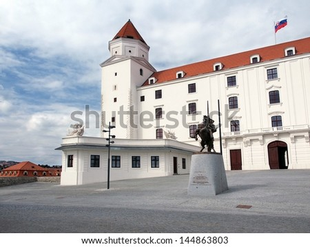 Summer view of honorary courtyard and main entrance gate to Bratislava Castle, Slovakia. Statue of Svatopluk (Great Moravian King) can be seen in foreground. - stock photo