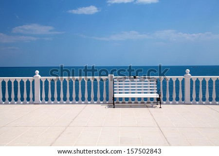 Summer view with classic white balustrade, bench and empty terrace overlooking the sea (Italy) - stock photo