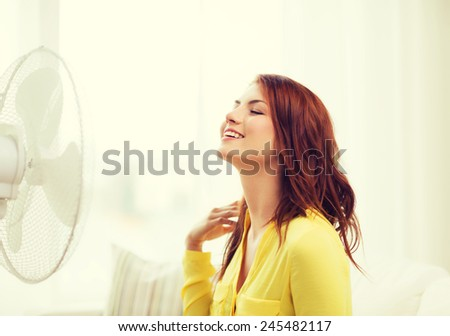summer, weather and equipemt concept - smiling redhead teenage girl with big fan at home - stock photo