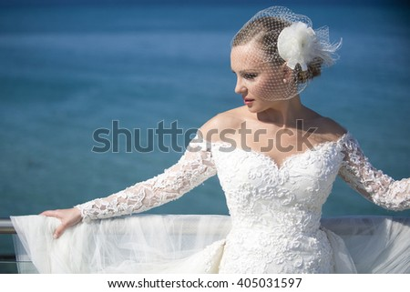 Summer wedding.Beautiful bride on the sea. Romantic beautiful bride in white dress posing on terrace with sea in background - stock photo