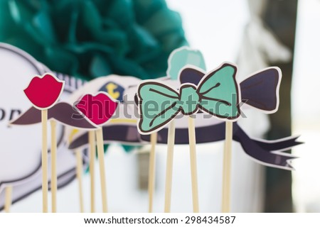 Summer wedding decoration for party. Served banquet table. Sea style. Paper pompons. Wedding accessories. Photo booth props and design elements. Party Set - glasses, hats, crowns, lips, mustaches.  - stock photo