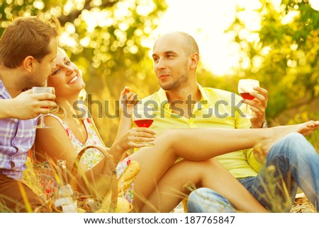Summer weekend concept. Portrait of happy group of friends in trendy casual clothing drinking red wine, talking and having fun. Sunny day. Copy-space. Outdoor shot - stock photo