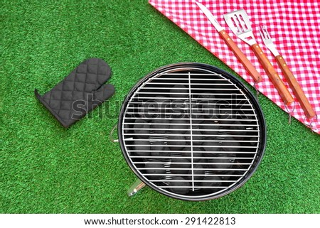 Summer Weekend Or Holiday BBQ Grill Party Or Picnic Concept. Park Or Backyard Fresh Lawn In the Background. Portable Kettle Charcoal Grill And Tools Close-up - stock photo