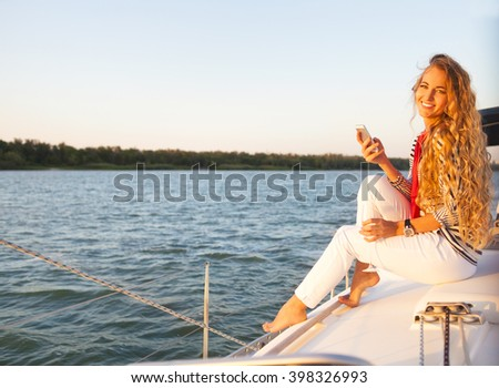 Summer woman on boat taking a picture by mobile phone - stock photo