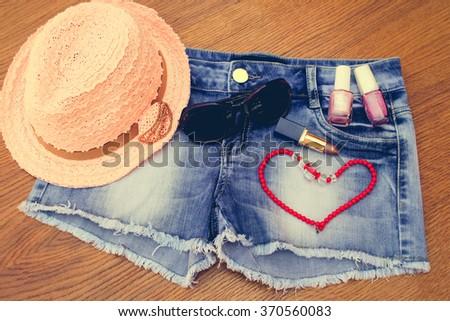 Summer women's accessories: red sunglasses , beads, denim shorts, sun hat, nail polish, lipstick open.  Toned image.  - stock photo