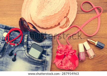 Summer women's accessories: sunglasses, beads, denim shorts, mobile phone, headphones, a sun hat, handbag, lipstick, nail polish. Toned image  - stock photo