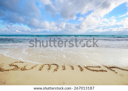 Summer word written on sand being washed out with tide - stock photo