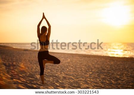 Summer yoga session on a beautiful golden beach - polish Grzybowo village, near to Kolobrzeg. Vriksha-asana - tree pose. - stock photo