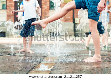 Summertime enjoyment. Kids legs and feet wet in fountain. Outdoors. - stock photo