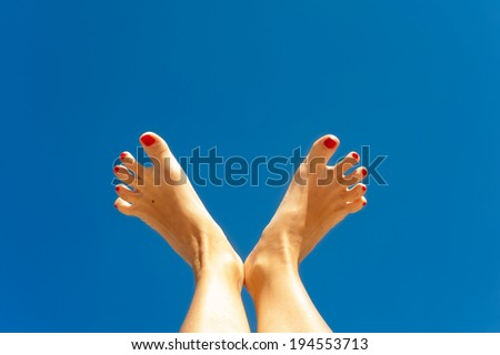 Summertime enjoyment. Woman feet on blue sky background. Outdoors. - stock photo