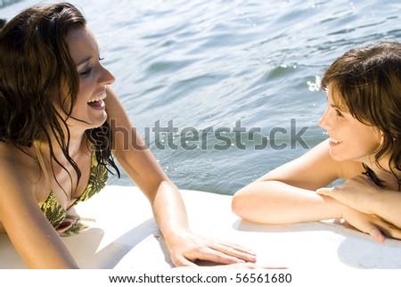 Summertime - Girls having fun on surfboard - stock photo