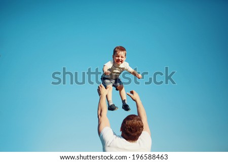 Summertime! Happy joyful child, father fun throws up son in the air, carefree, blue sky, family, travel, vacation, childhood, father's day - concept. Sunlight on the sunset - stock photo