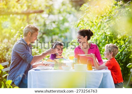 Summertime, nice family, Daddy, Mom and their two kids sitting at a table, eating lunch in the garden enjoying a sunny day - stock photo