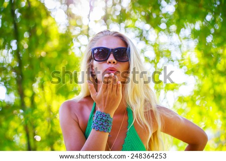 Summertime portrait of beautiful young blonde woman in a green bikini and sunglasses  sending an air kiss - stock photo