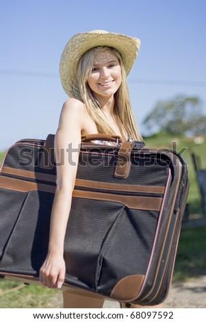 Summertime Traveling Tourist Woman Carrying Her Travel Bag Under One Arm Smiles While On Summer Holidays - stock photo