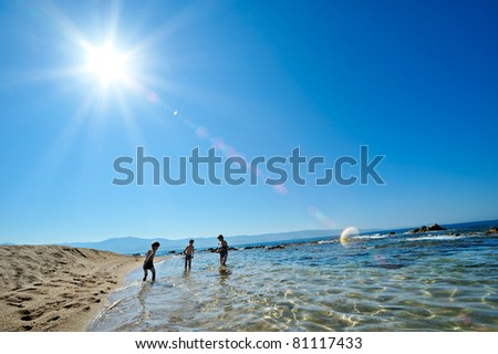 summertime - two boys and their mother playing on the beach - stock photo