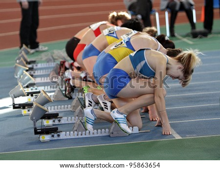 SUMY, UKRAINE - FEB.17: Unidentified girls on the start of the 60 meters dash during the Ukainian Track and Field Championships on February 17, 2012 in Sumy, Ukraine. - stock photo