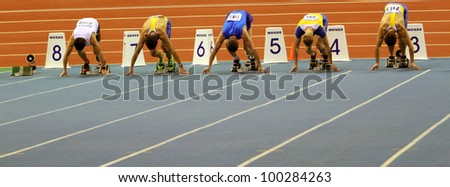 SUMY, UKRAINE -FEB.16: Unidentified men compete in the start of the 60 meters dash during the Ukrainian Track and Field Championships on February 16, 2012 in Sumy, Ukraine. - stock photo
