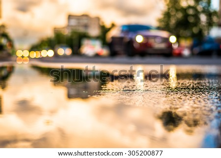 Sun after the rain in the city, view of the approaching car with a level of puddles on the pavement - stock photo