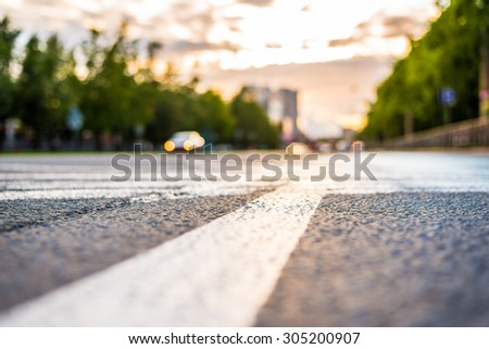 Sun after the rain in the city, view of the approaching car with the level dividing line - stock photo