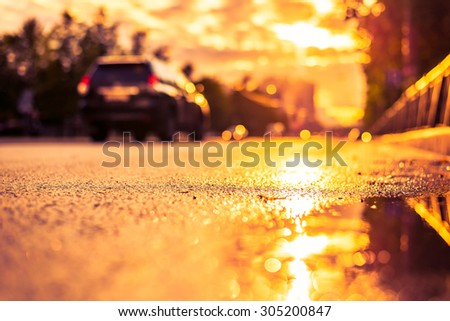 Sun after the rain in the city, view of the car with a level of puddles on the pavement. Image in the yellow-purple toning - stock photo