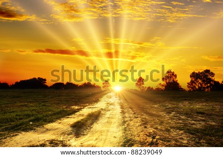 sun and clouds over field with road - stock photo