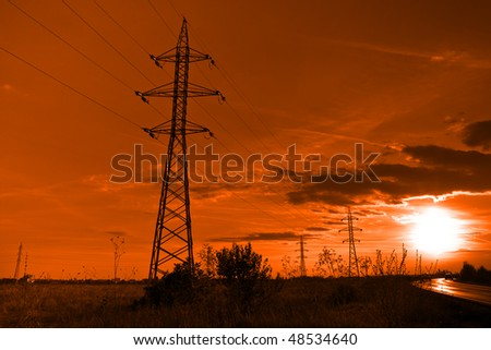 Sun and electricity - powerline towers at sunset - stock photo